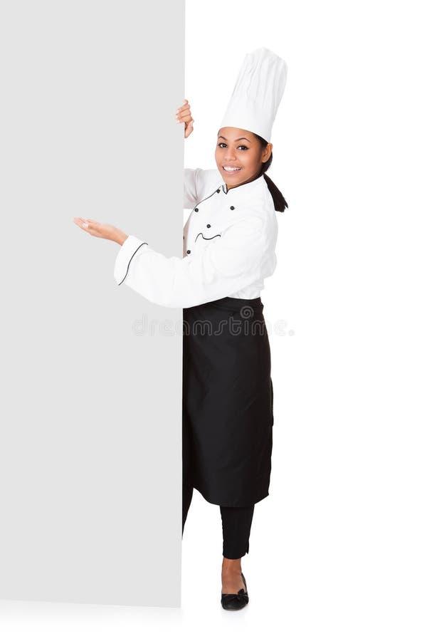 Vrouwelijke Cook die zich achter het Aanplakbiljet bevinden stock fotografie