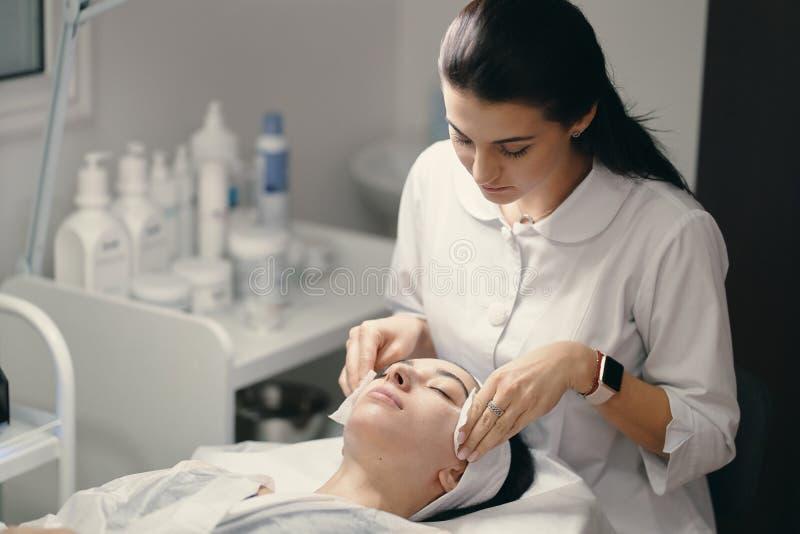 Vrouwelijke cosmetologist die gezichtsbehandeling maken aan een mooie woma royalty-vrije stock afbeeldingen