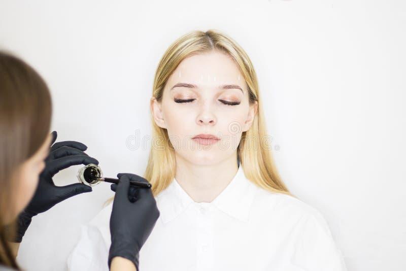 Vrouwelijke cosmetologist voert wenkbrauwcorrectie op mooie modellen in de schoonheidssalon uit Het gezicht van het meisje is een stock foto