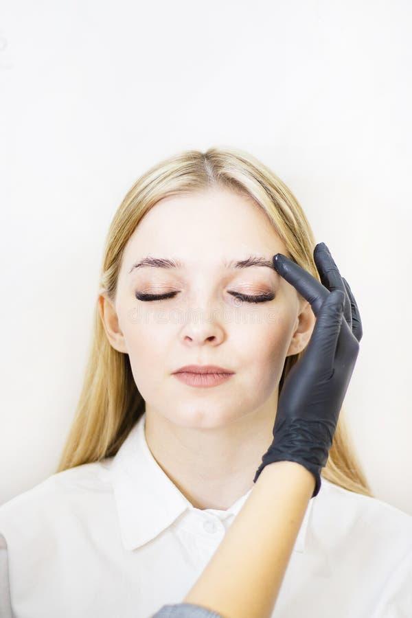 Vrouwelijke cosmetologist voert wenkbrauwcorrectie op mooie modellen in de schoonheidssalon uit Het gezicht van het meisje is een stock foto's