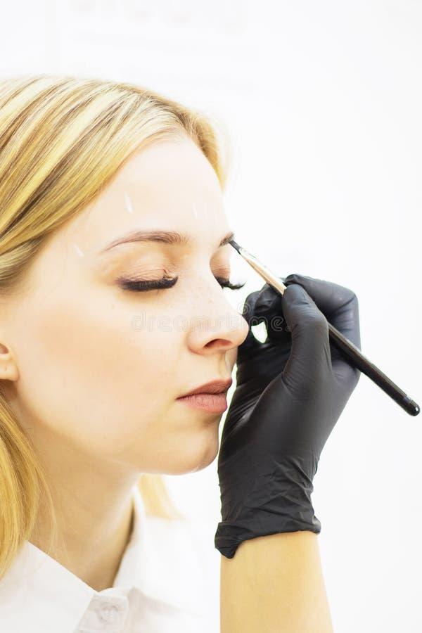 Vrouwelijke cosmetologist voert wenkbrauwcorrectie op mooie modellen in de schoonheidssalon uit Het gezicht van het meisje is een royalty-vrije stock foto's