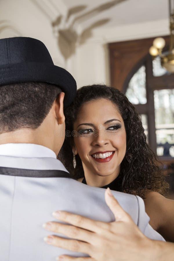 Vrouwelijke Danser Looking Away While die Tango met de Mens uitvoeren stock afbeeldingen