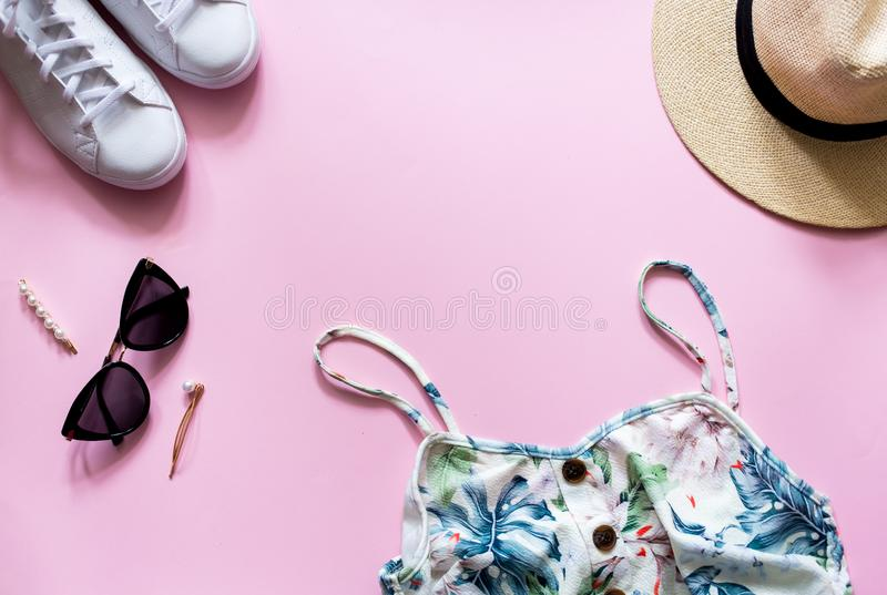 Vrouwelijke de zomeruitrusting op roze backgroud Gedrukte de zomerkleding met strohoed, zonnebril en witte tennisschoenen stock fotografie
