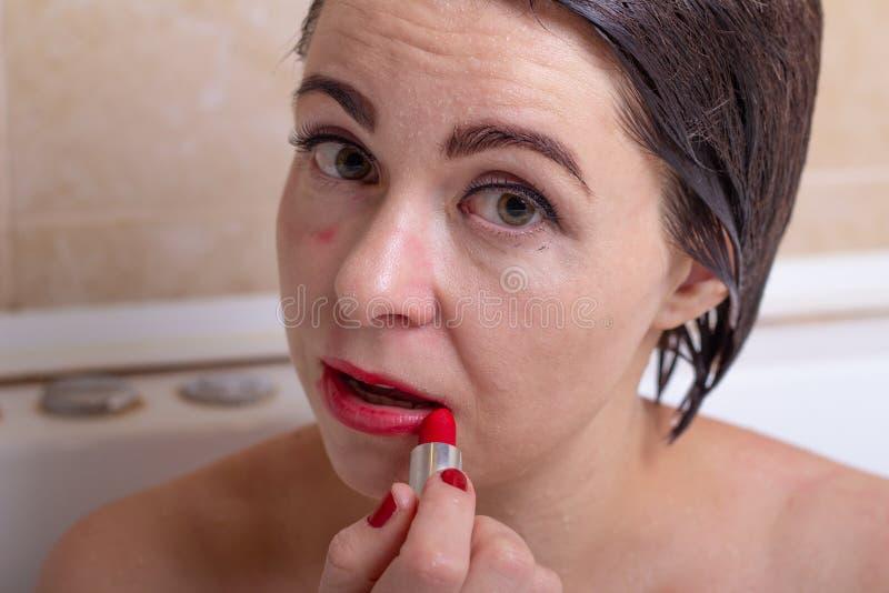 Vrouwelijke depressie een vrouw in de badkamers met een van angst verstijfde lippenstift van blikschuine strepen op haar gezicht stock foto