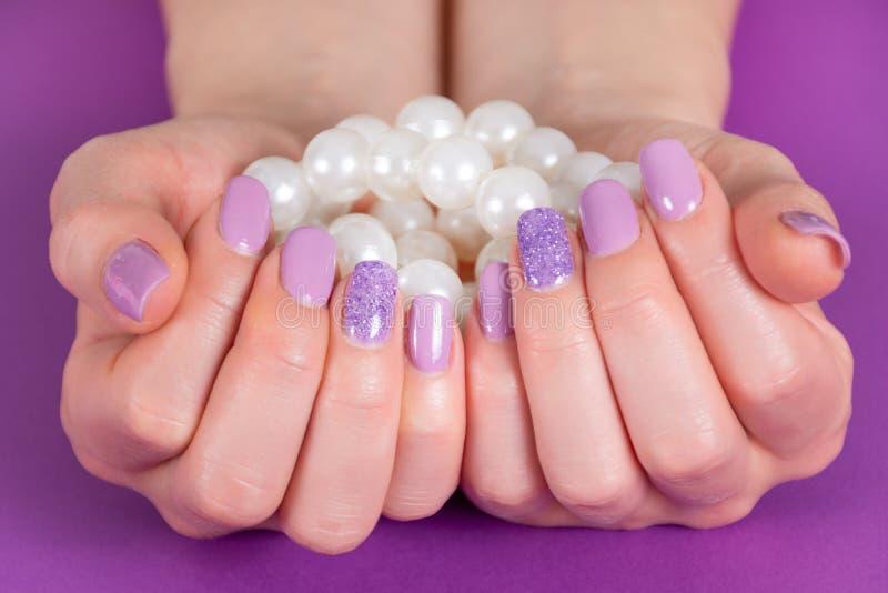 Vrouwelijke die hand met een lilac de holdingsstapel van de kleurenmanicure van parels op purpere achtergrond worden geïsoleerd stock afbeelding