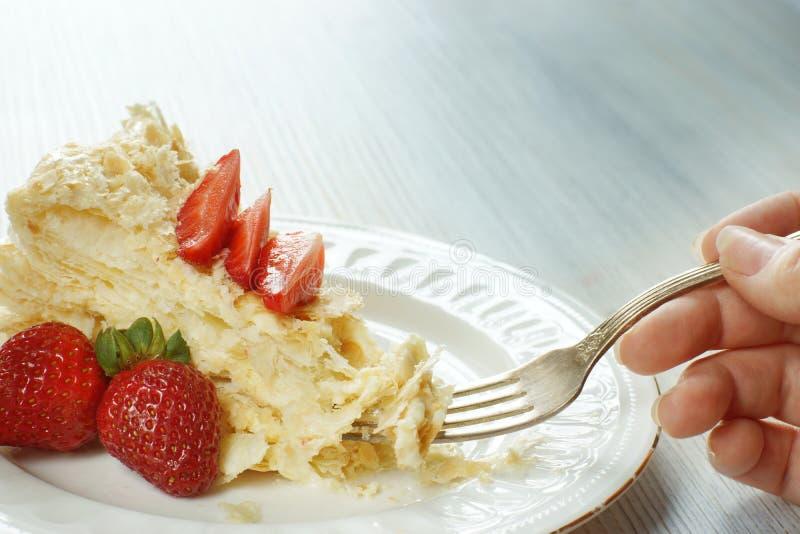 Vrouwelijke die hand met een vork en een stuk van cake Napoleon, met aardbeien wordt verfraaid royalty-vrije stock foto