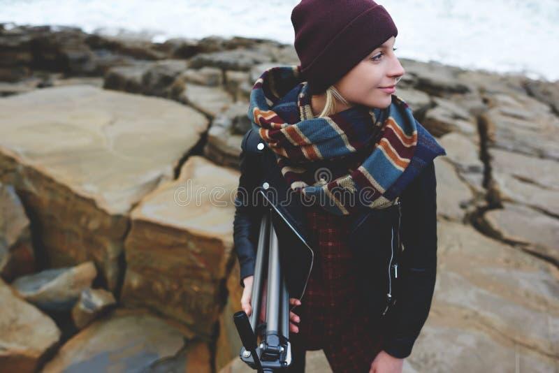 Vrouwelijke die toerist in warme sjaal omhoog wordt verpakt die verbazend aard op een klip genieten van stock foto's