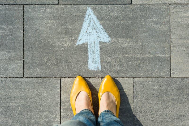 Vrouwelijke die voeten met pijl op het asfalt wordt geschilderd stock foto