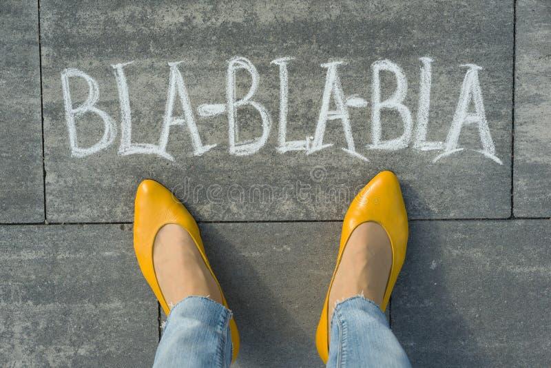 Vrouwelijke die voeten met tekstbla-bla-bla op grijze stoep worden geschreven royalty-vrije stock fotografie