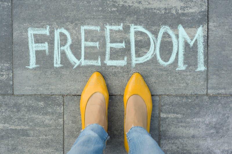Vrouwelijke die voeten met tekstvrijheid op grijze stoep wordt geschreven royalty-vrije stock foto's