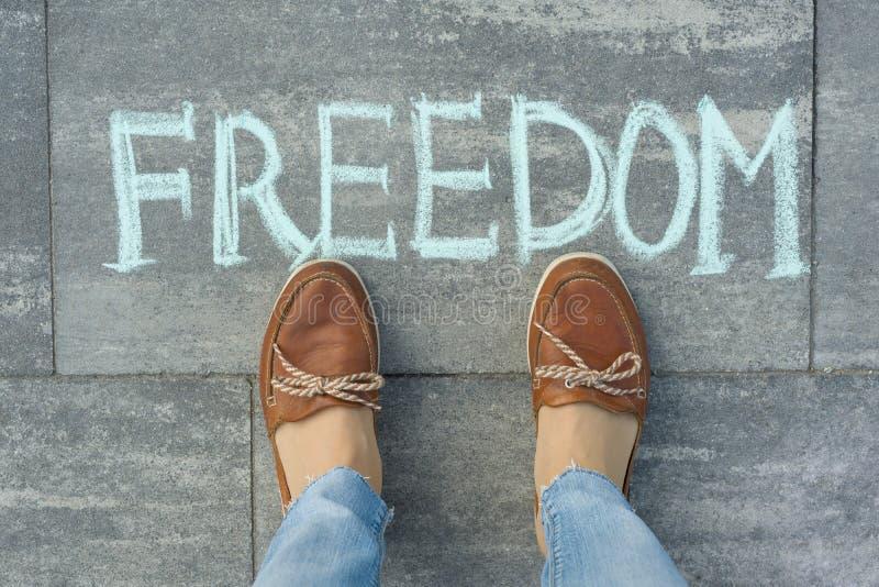 Vrouwelijke die voeten met tekstvrijheid op grijze stoep wordt geschreven royalty-vrije stock foto