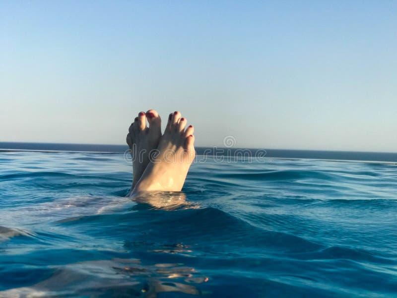 Vrouwelijke die voeten, voeten met vingers uit met rode manicure in mooi blauw nat blauw natuurlijk duidelijk water tegen een ach royalty-vrije stock foto