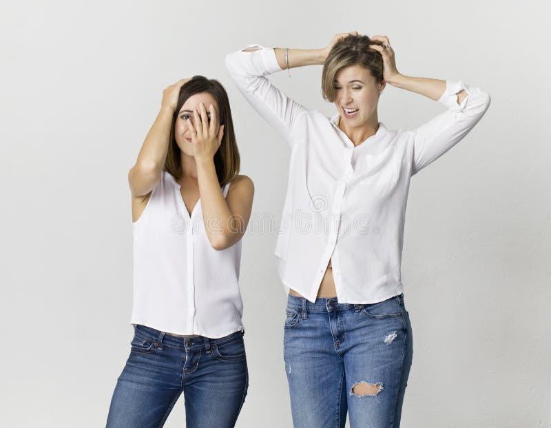 Vrouwelijke die vriend twee bij studioachtergrond wordt verrast, op wit wordt geïsoleerd stock afbeelding