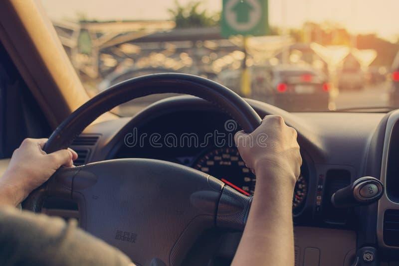 Vrouwelijke drijfauto op de weg met zonlicht uitstekende filter stock foto