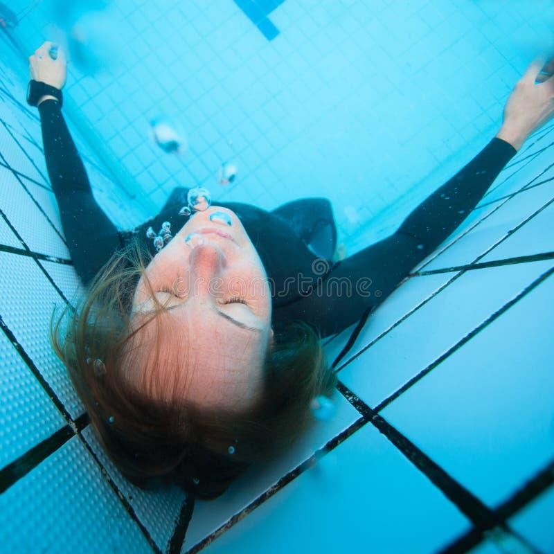 Vrouwelijke duiker met gesloten ogen onderwater in zwembad royalty-vrije stock afbeelding