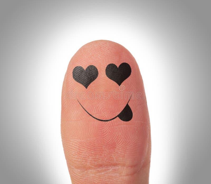 Vrouwelijke duimen met glimlachgezicht op de vinger stock fotografie