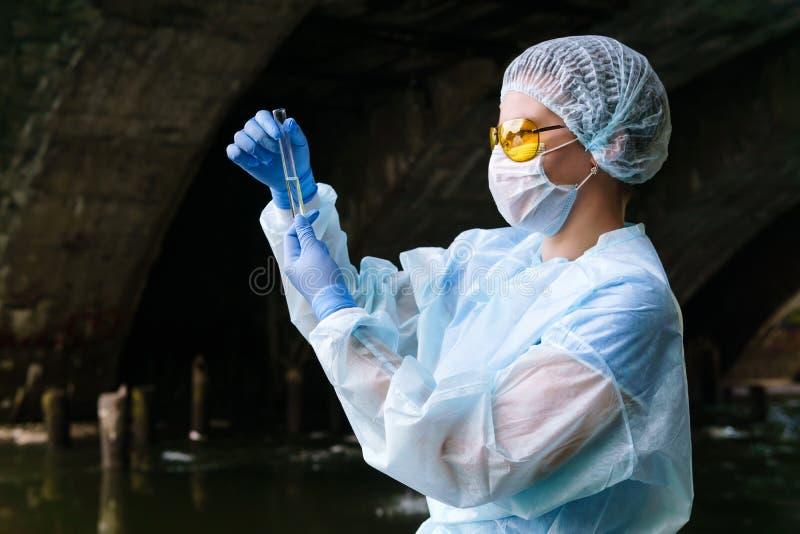 Vrouwelijke ecoloog of biochemist onderzoekt een reageerbuis met water uit een stadsrivier in een collector royalty-vrije stock fotografie