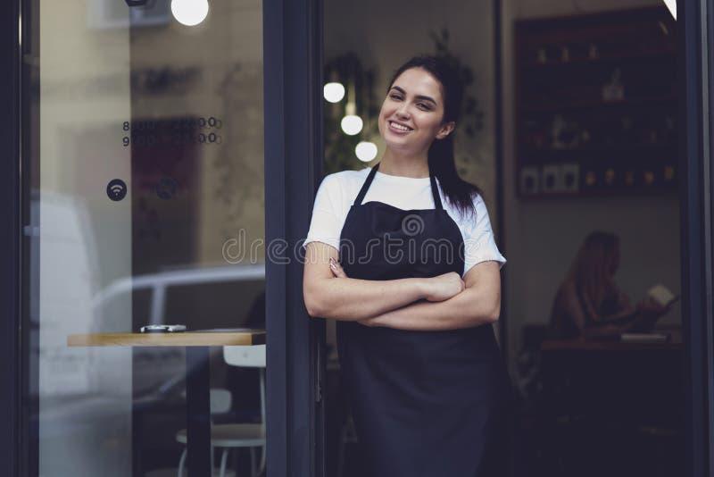 Vrouwelijke eigenaar van restaurant met glimlach die zich dichtbij de ingang van de koffiedeur bevinden royalty-vrije stock afbeelding