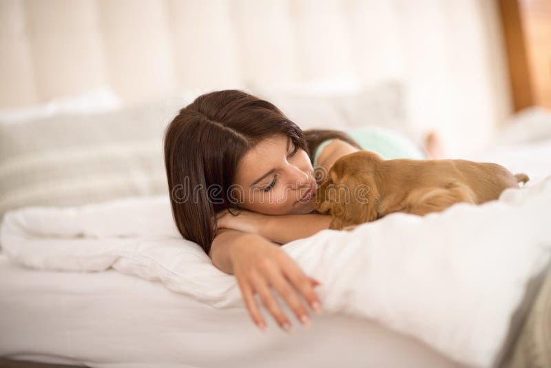 Vrouwelijke eigenaarslaap met puppyhuisdier royalty-vrije stock foto's