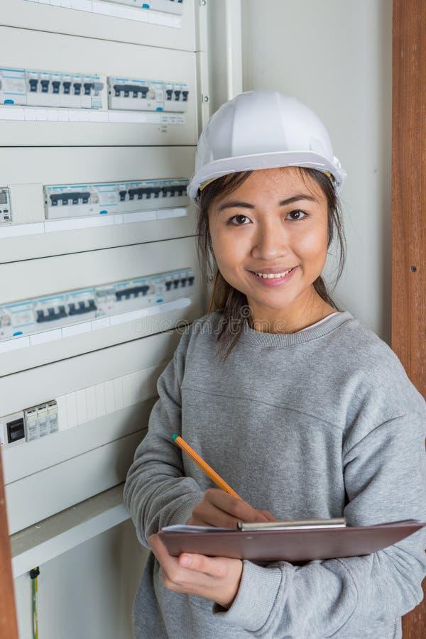 Vrouwelijke elektricien die aan electical zekeringsraad werken stock afbeeldingen