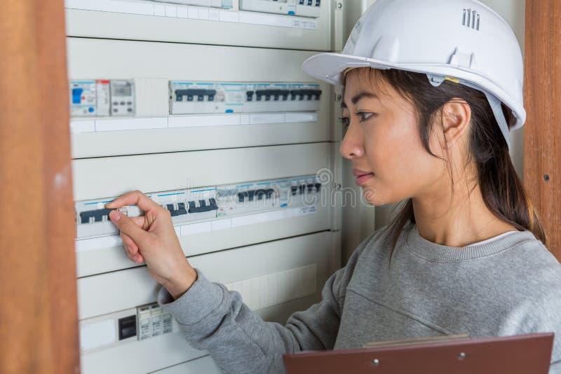 Vrouwelijke elektricien die aan zekeringsraad werken royalty-vrije stock foto's