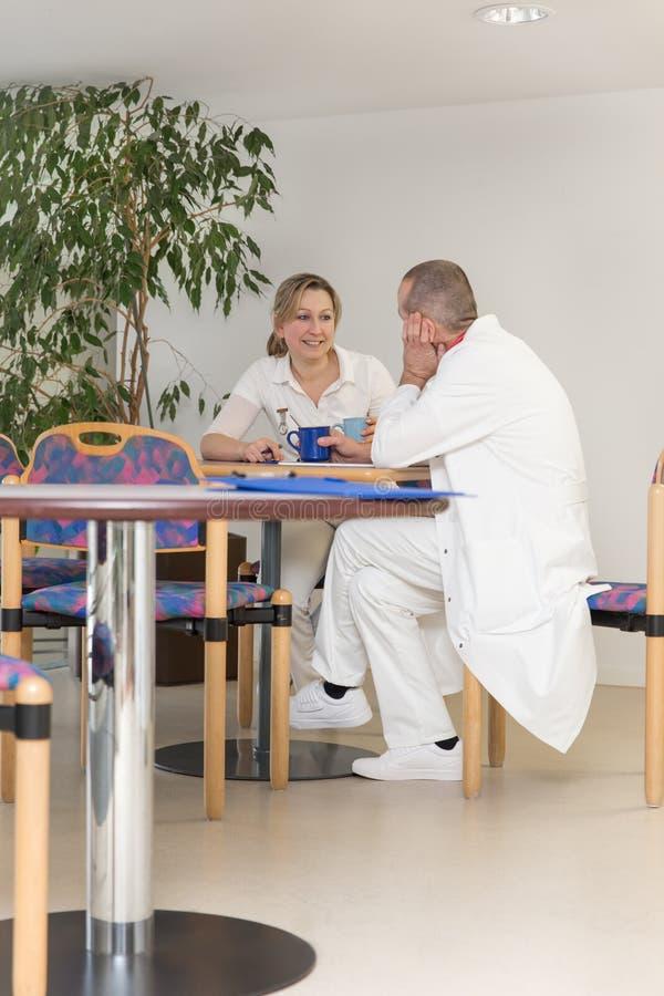 Vrouwelijke en mannelijke arts in breakroom van het ziekenhuis stock foto