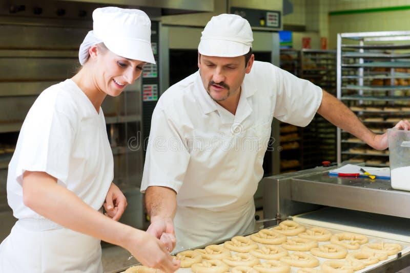 Vrouwelijke en mannelijke bakker in bakkerij royalty-vrije stock afbeelding