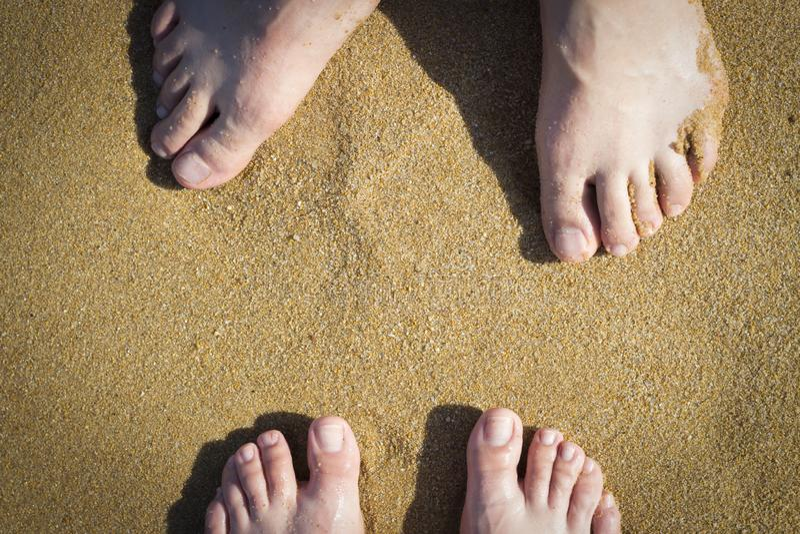 Vrouwelijke en mannelijke benen op zand, hoogste mening stock afbeeldingen