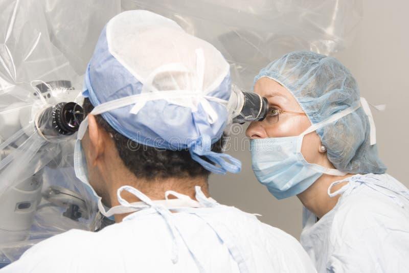 Vrouwelijke en Mannelijke Chirurgen die het Werken gebruiken stock afbeeldingen