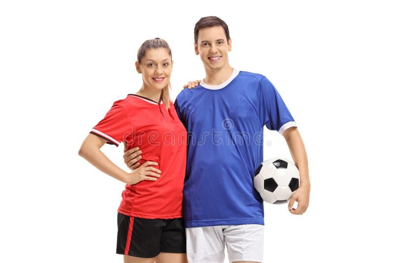 Vrouwelijke en mannelijke voetballers met een voetbal stock foto's