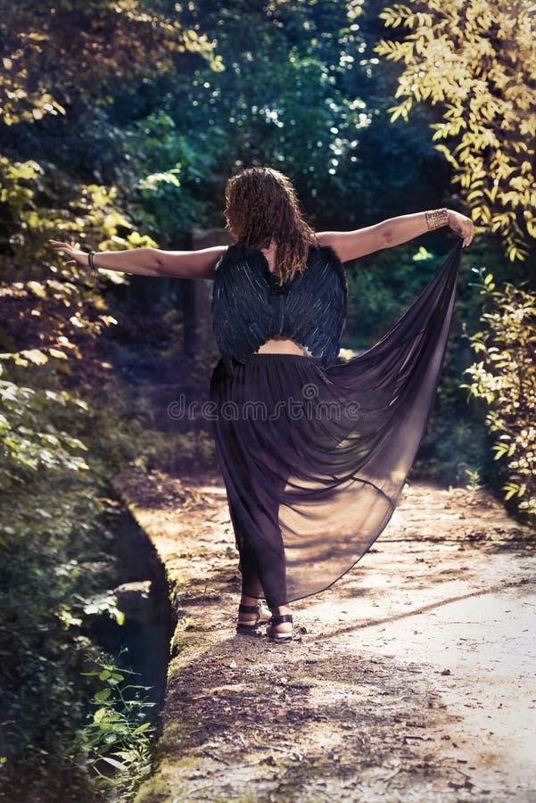 Vrouwelijke engel met zwarte vleugels op een zwarte achtergrond royalty-vrije stock foto's