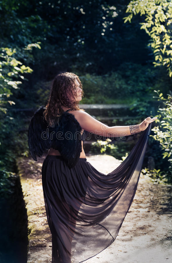 Vrouwelijke engel met zwarte vleugels op een zwarte achtergrond royalty-vrije stock foto