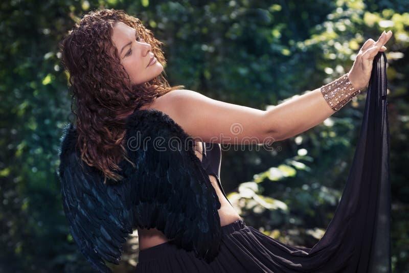 Vrouwelijke engel met zwarte vleugels op een zwarte achtergrond royalty-vrije stock afbeelding