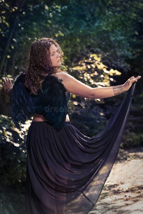 Vrouwelijke engel met zwarte vleugels op een zwarte achtergrond stock afbeelding