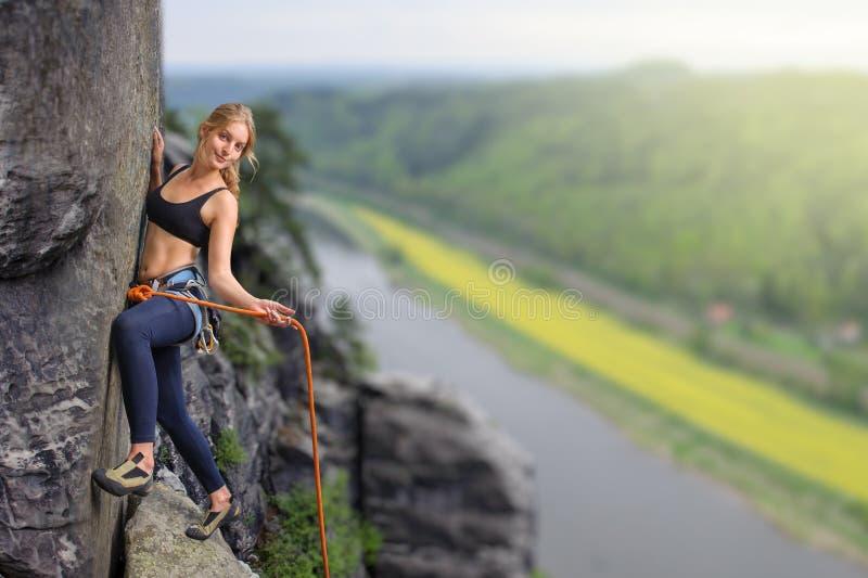 Vrouwelijke extreme klimmer die rots over de rivier beklimmen stock afbeeldingen