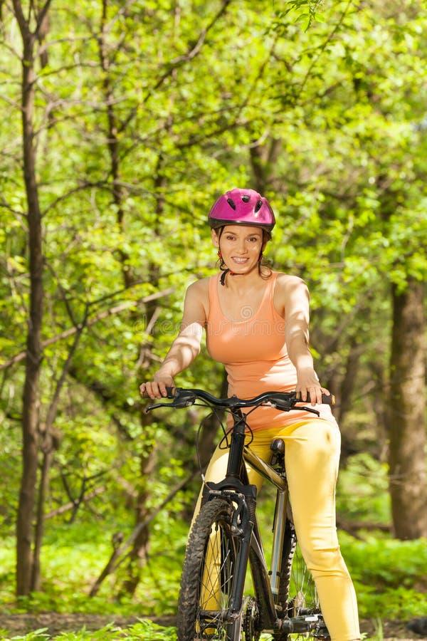 Vrouwelijke fietser die de lente van bosmening genieten stock foto's