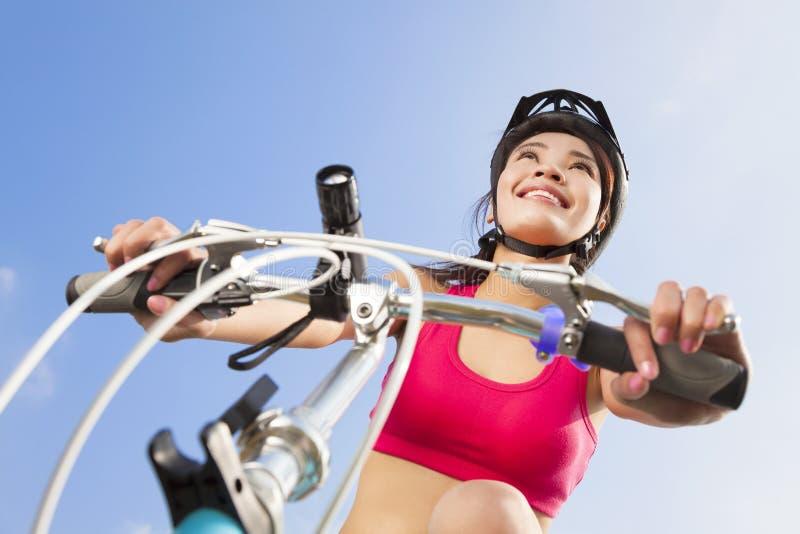 Vrouwelijke fietser die met blauwe hemelachtergrond beginnen te berijden royalty-vrije stock fotografie