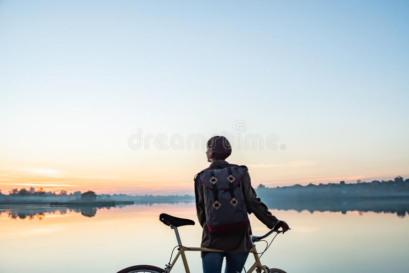 Vrouwelijke fietser die van mooie blauwe uurscène genieten door het meer W royalty-vrije stock afbeelding