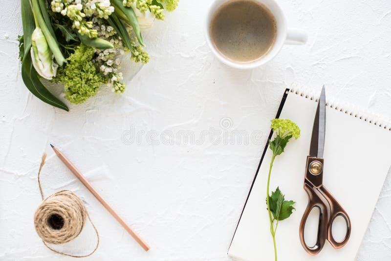Vrouwelijke flatlay met bloemen en ccoffee op wit tafelblad royalty-vrije stock foto