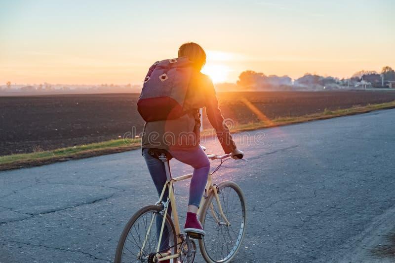 Vrouwelijke forens die een fiets berijden uit stad aan een gebied in de voorsteden wo royalty-vrije stock afbeelding