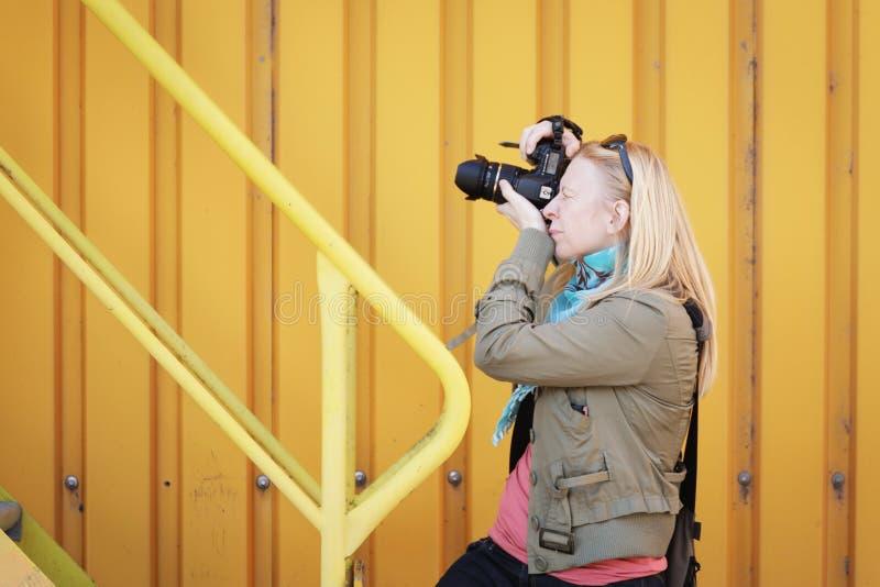Vrouwelijke fotograaf die in openlucht met haar dslr schieten Fotografie, creativiteit en hobbyconcept stock fotografie