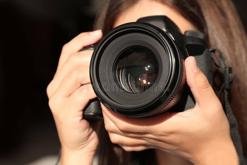 Vrouwelijke fotograaf met professionele camera op donkere achtergrond stock fotografie