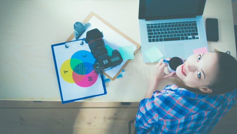 Download Vrouwelijke Fotograafzitting Op Het Bureau Met Laptop Stock Afbeelding - Afbeelding bestaande uit wijfje, zitting: 107705461