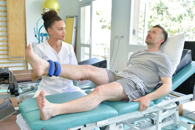 Vrouwelijke fysiotherapeut die beenpatiënt masseren stock fotografie