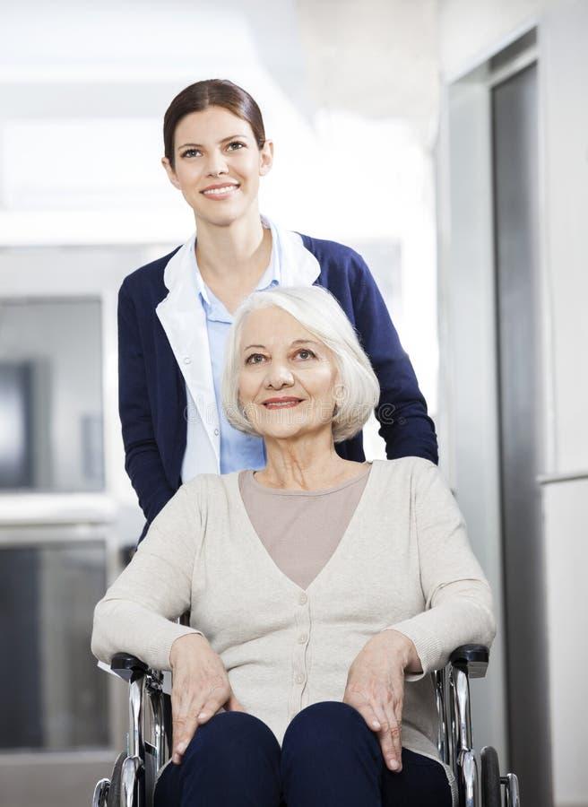 Vrouwelijke Fysiotherapeut Pushing Senior Woman in Rolstoel royalty-vrije stock afbeelding