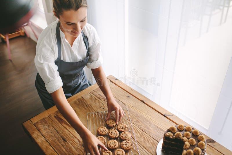 Vrouwelijke gebakjechef-kok die koekjes voorbereiden royalty-vrije stock foto's