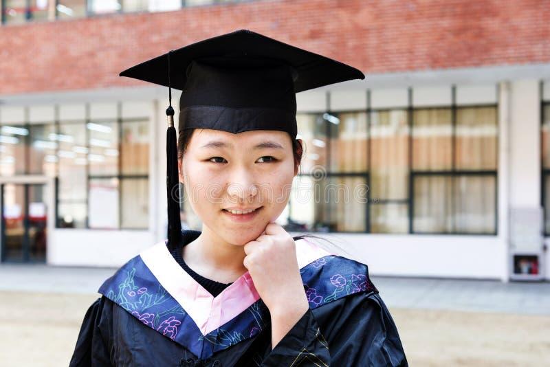 Vrouwelijke gediplomeerde die een graduatietoga dragen royalty-vrije stock afbeelding