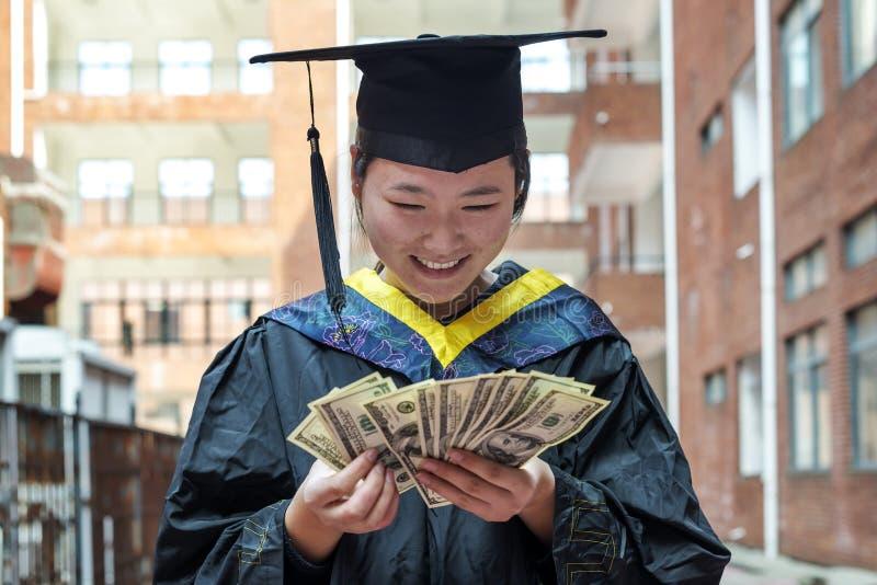 Vrouwelijke gediplomeerde die een graduatietoga dragen stock foto's