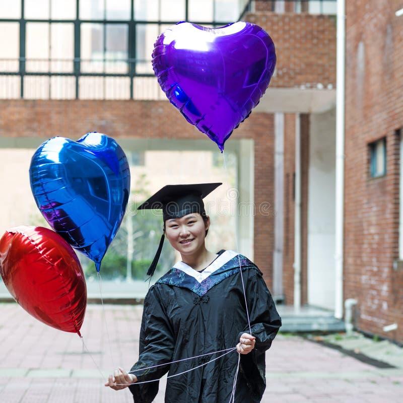 Vrouwelijke gediplomeerde die een graduatietoga dragen royalty-vrije stock fotografie