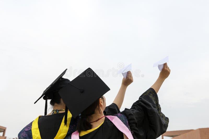 Vrouwelijke gediplomeerde dragende graduatietoga stock foto